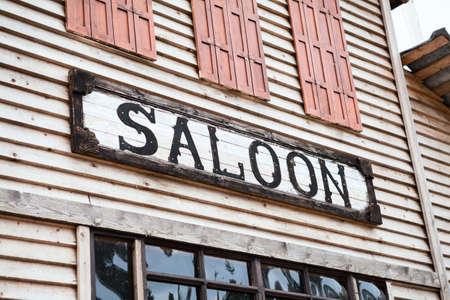 ortseingangsschild: Saloon Zeichen auf Gebäudefassade