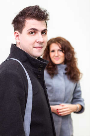 Man in black coat and girl behind on white background photo