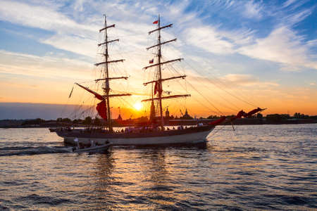 Sailing vessel on the background of the Peter and Paul fortress in the rays of the setting sun photo