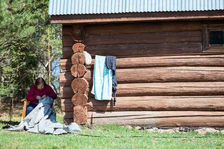 Senior needlewoman repairing tissue, working near wooden house photo