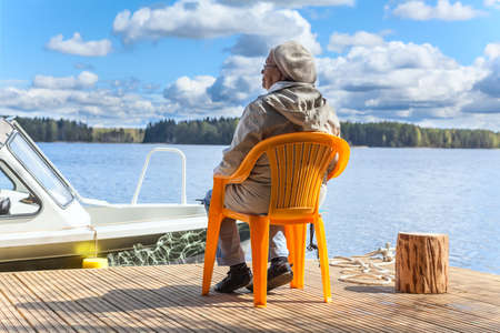Elderly Caucasian woman relaxing at the lake on pier photo