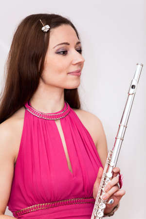 silver flute: Portrait of flutist woman in red dress with silver flute