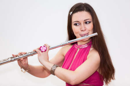 silver flute: Young Caucasian woman a flutist playing on flute, white background