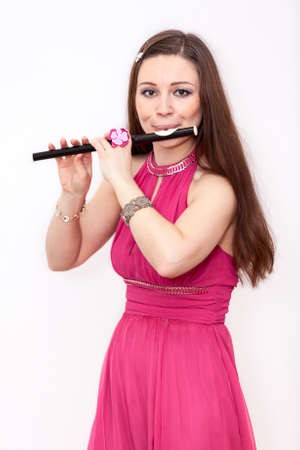 silver flute: Beauty Caucasian woman a flutist playing on small flute, white background