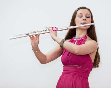 silver flute: Young woman in red dress playing on flute, white background