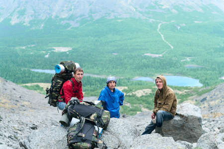 Mature father, mother and son hiking in mountains together photo