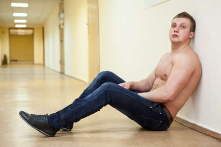 wistfulness: Depressive man shirtless sitting in long corridor