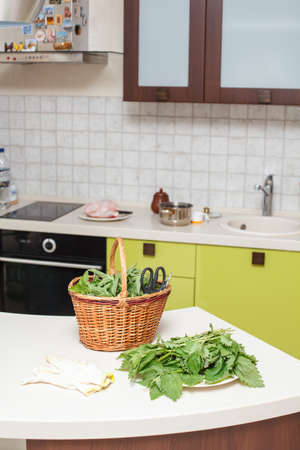 Nettle in basket is on the kitchen photo