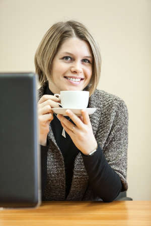 Smiling beauty woman holding coffee mug in hands photo