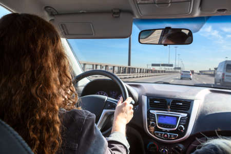 Caucasian woman driving car on highway, inside view Banque d'images
