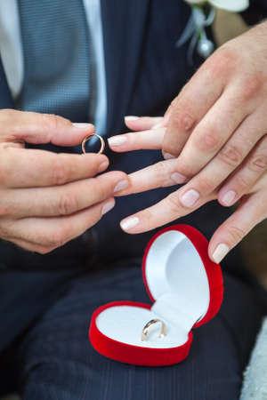 Groom wearing wedding ring on bride finger photo