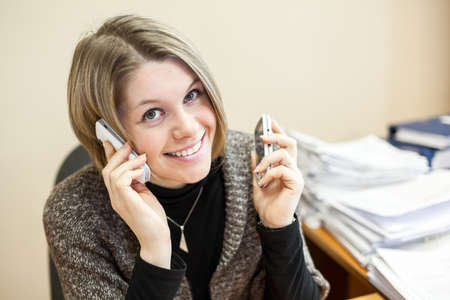 Cheerful woman talking on the two phones at the same time photo