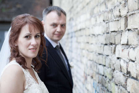 Faces of bride and groom against brick wall photo