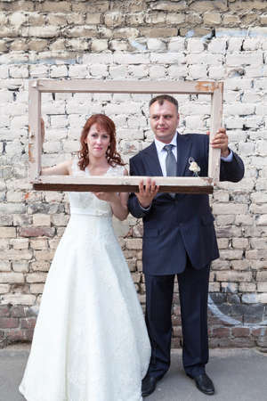 Full length of bride and groom looking through the portrait frame