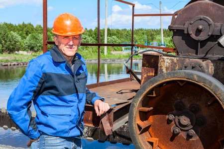 Engineer worker standing near sewage treatment mechanism photo