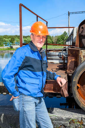 Senior man mechanist standing near sewage treatment plant photo