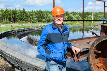 Senior workman with orange hardhat in sewage treatment plant photo