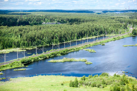 Rail road aerial view with evergreen woods and blue lakes photo