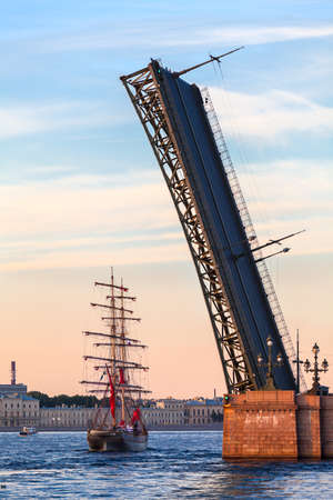 SAINT-PETERSBURG, RUSSIA - CIRCA JUNE, 2013  Sailfish with Red sails passing under opened span of the Trinity bridge on Neva river during the White Nights Festival  Vessel is a symbol of the end of school year photo