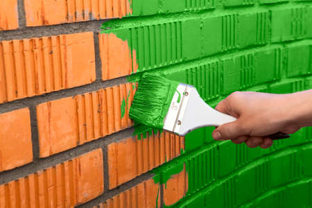flat brush: Human hand painting the wall with green color
