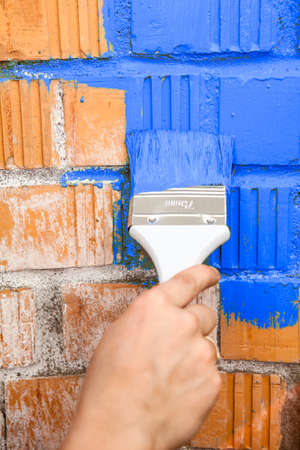 Orange brick wall painted with blue colour photo