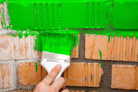 Paint brush with green colour on brick wall photo