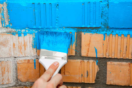 white color worker: Paint brush with blue colour on brick wall