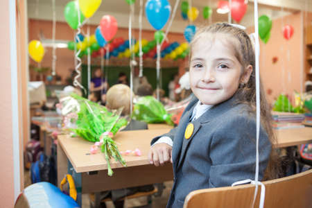 grade schooler: Smiling first grade pupil at the school desk looking back Stock Photo