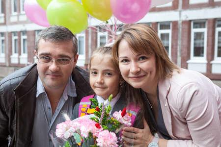 grade schooler: Portrait of happy parents with a schoolgirl on the threshold of the school