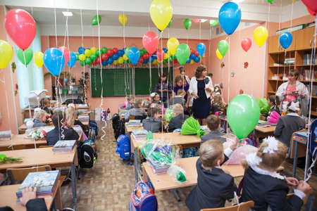 grade schooler: SAINT-PETERSBURG, RUSSIA - SEPTEMBER, 1, 2013: Pupils sit in the classroom at first lesson in elementary Russian school. Celebration of back to school in September, 1