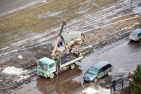 dirty car: SAINT-PETERSBURG, RUSSIA - CIRCA FEBRUARY, 2014: Tow truck loads banding after road crash freight car for scrappage. Government scrappage scheme Editorial
