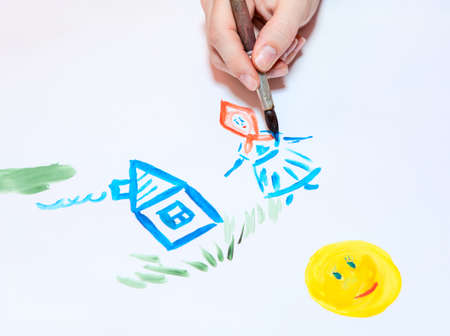 Hand drawing funny house and woman with sun on white sheet of paper photo