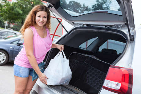 woman holding bag: Pretty woman holding bag with food neaar trunk of pov