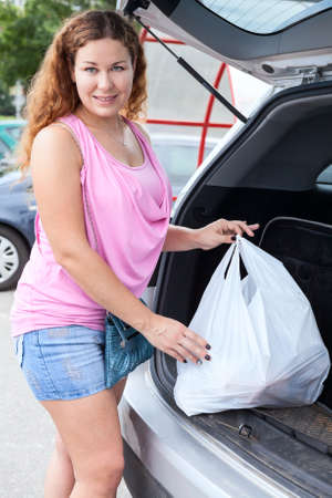 Attractive young woman near own car with shopping bag photo