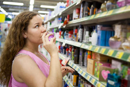 purchaser: Woman purchaser smelling perfume in shop