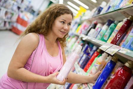cleaning products: Mujer caucásica joven que sostiene la limpieza de detergente en la tienda