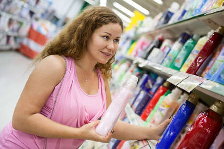 Young Caucasian woman holding cleaning detergent in shop photo