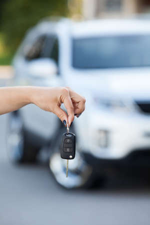 Suv defocused on background and woman hand with ignition key photo