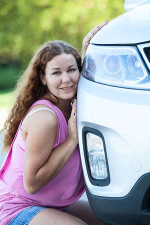 Attractive woman in pink blouse leaning her cheek to the car photo