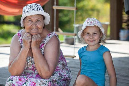 amigos abrazandose: Sonriendo abuela senior y feliz nieto sentado en la terraza de verano Foto de archivo