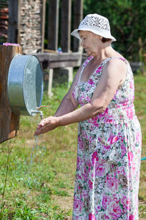 senior adult woman: Elderly Caucasian woman washes her arms outdoor Stock Photo
