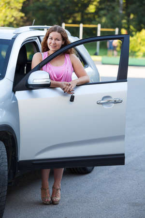 Pretty woman standing side of car with opened door photo