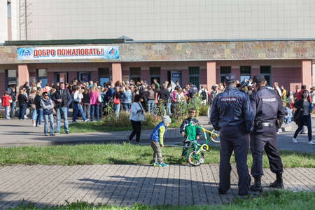SAINT-PETERSBURG, RUSSIA - CIRCA AUGUST, 2014: Police officers look at crowd of people in queue to buy swimming season ticket for kids. A small quantity of budgetary places for children in sports department.