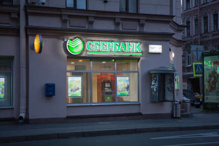 bank branch: SAINT-PETERSBURG, RUSSIA - CIRCA AUGUST, 2014: Neon sign of Sberbank of Russia is on facade of building at night. Sberbank is the large state bank in Russia Editorial