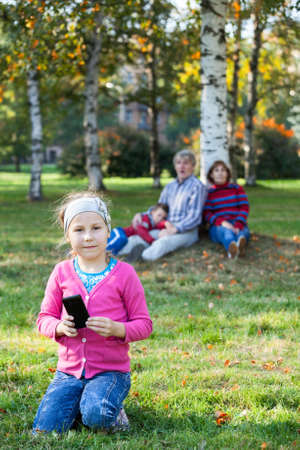 Young girl looking at camera when sitting on grass with cellphone, family on background