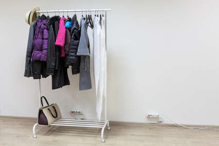 outerwear: Floor rack with outerwear in the interior of white hallway room, copyspace