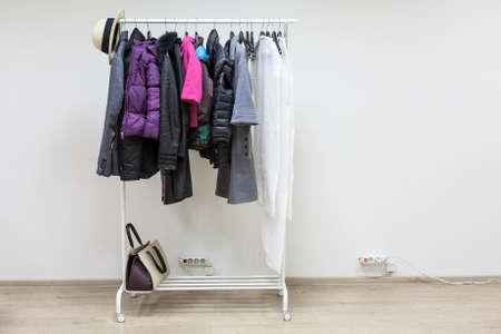 outerwear: Femminile e maschile bianco e nero outerwear appeso su un rack pavimento Archivio Fotografico