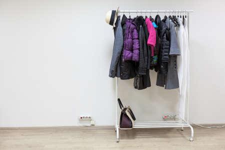 outerwear: Rack con capispalla in piedi sul pavimento della stanza corridoio bianco, copyspace