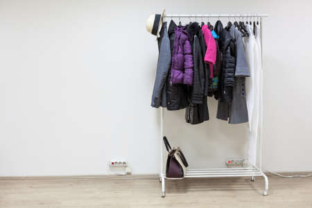 vestibule: Rack with outerwear standing on the floor of white hallway room, copyspace