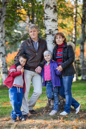Four people family full length portrait in autumn park photo